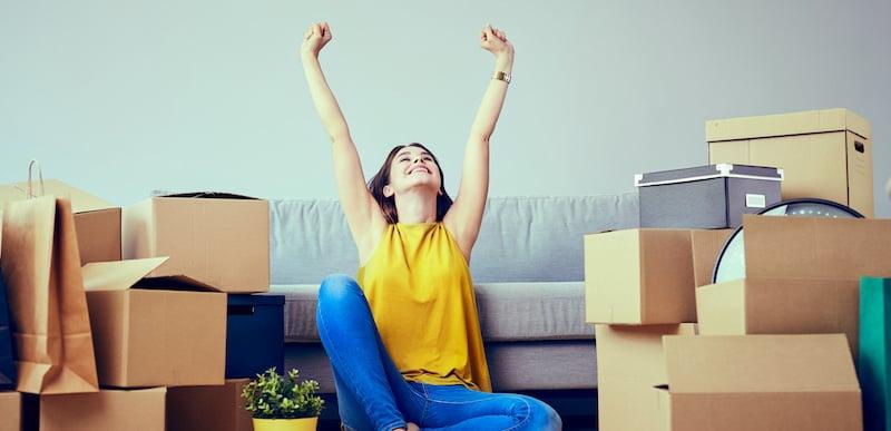 jeune femme heureuse dans son appartement avec des cartons qui lève les bras en l'air