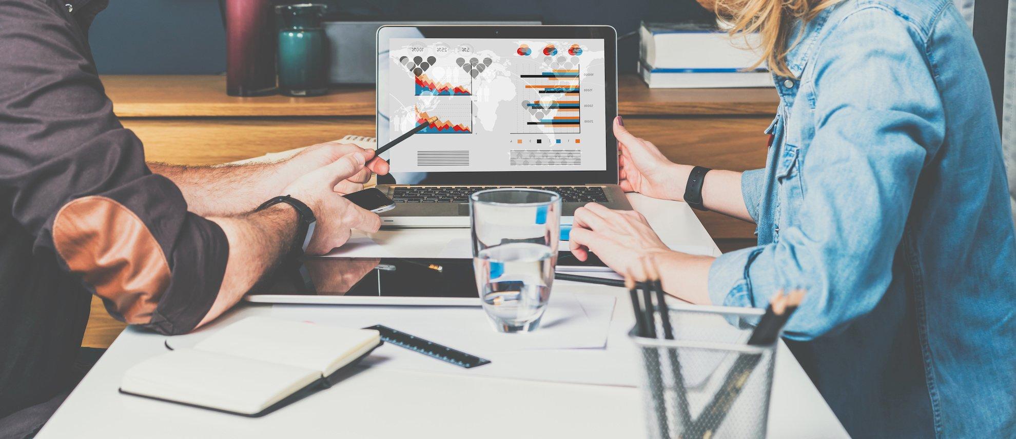 Photo centrée sur un ordinateur d'un homme et une femme qui regarde des statistiques
